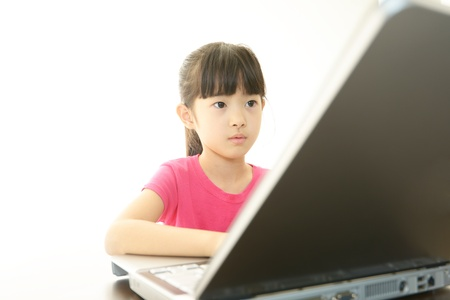 Smiling teenage girl using a laptop photo