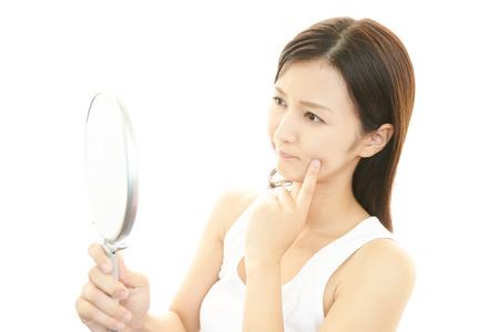 Mujer curiosa que mira el espejo comprobando su cara Foto de archivo