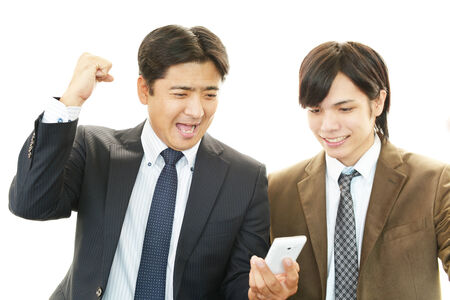 liveliness: Happy men holding smart phone Stock Photo