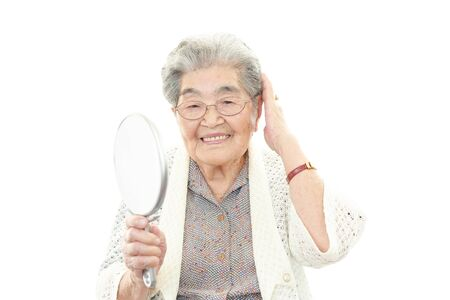Old woman taking care of her hair photo