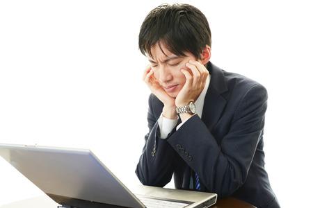 Stress Asian man looking at laptop  写真素材