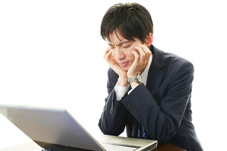 Stress Asian man looking at laptop  Banque d'images