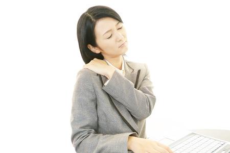 dolor hombro: Mujer de negocios que tiene un dolor en el hombro Foto de archivo