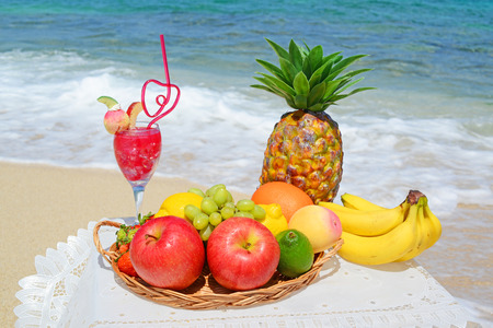 Fruits with juice on the sandy beach photo