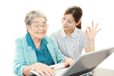 nursing class: Old woman using computer with a help by young woman