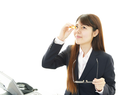 Asian woman dripping eye with eyes drops