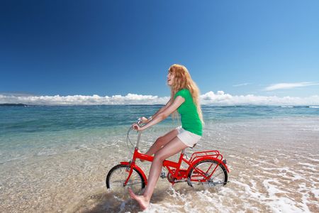Beautiful woman ride a bike on the beach photo