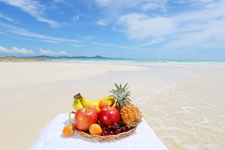 Exotic tropical fruit on plate on the sandy beach photo