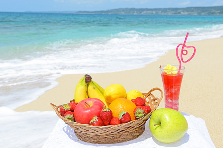 Tropical fruits on plate on the sandy beach photo