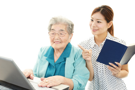 nursing class: Young woman teaching old woman to use laptop