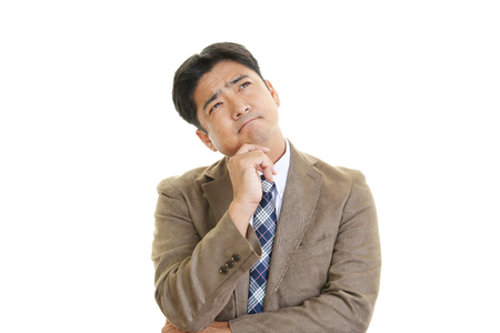 pay cuts: Depressed Asian businessman. Stock Photo