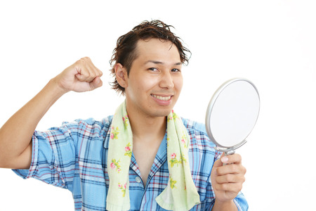 A man looking at himself in a hand mirror