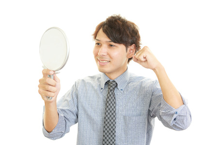 A man looking at himself in a hand mirror photo