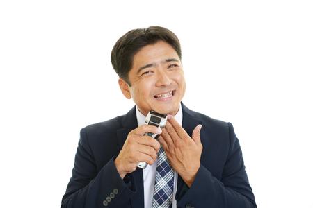 Asian man shaving with electric razor photo