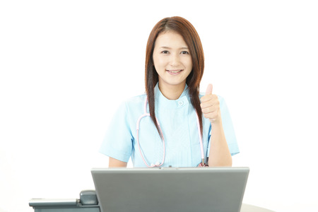 Smiling Asian female nurse with thumbs up photo