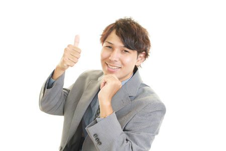 Smiling businessman with thumbs up photo
