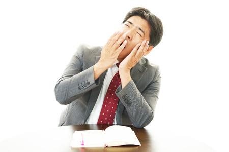 pay cuts: Sleepy Businessman yawning Stock Photo