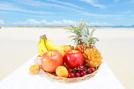 plum island: Tropical fruits in wicker basket on the sandy beach Stock Photo