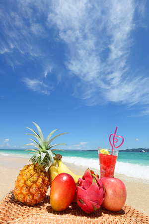 Tropical fruits with juice on the sandy beach photo