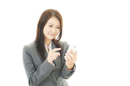 ビジネスの女性がスマート フォンを保持 写真素材