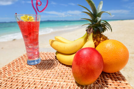 Fresh Fruits with juice on the beach photo