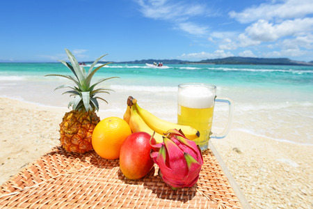 Tropical fruits with beer on the sandy beach photo