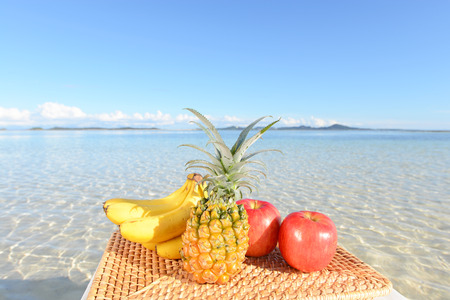 Fresh fruits on the sandy beach photo
