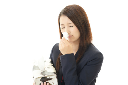 A woman blowing her nose photo