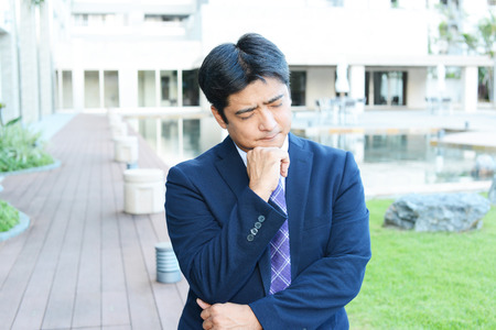 pay cuts: Portrait of a business man looking depressed Stock Photo