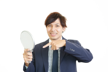 salaried worker: A man looking at himself in a hand mirror