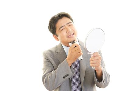 electric razor: Asian man shaving with electric razor