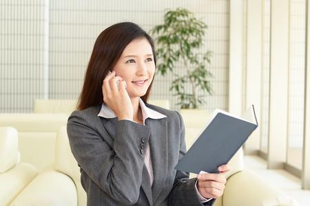 ビジネス女性スマート フォンを保持していると話しています。 写真素材