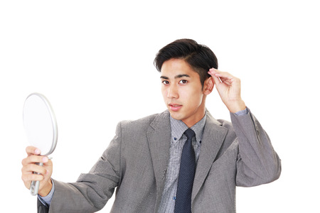 salaried worker: Asian man looking at his hair in mirror Stock Photo