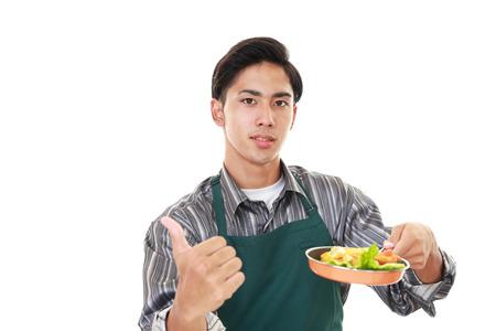 pan asian: Asian man wearing kitchen apron with pan Stock Photo