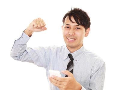 通信: Happy man holding a smart phone