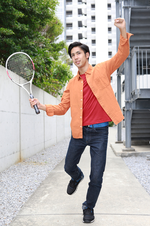 asian man face: Smiling Asian man with racket Stock Photo