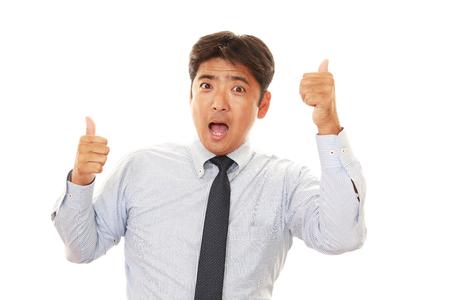 winner man: Business man at laptop, shows thumb up sign