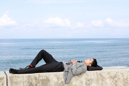 man lying down: Man lying down on seawall