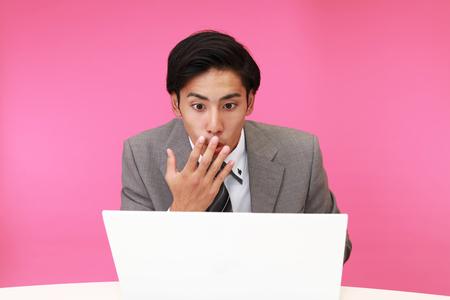 pink background: Surprised Asian businessman