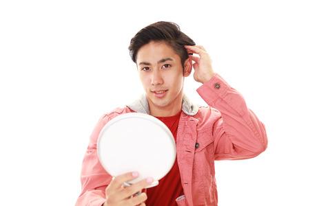 salaried: Asian man looking at his face in mirror Stock Photo