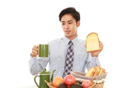 comiendo pan: Hombre asiático de desayunar