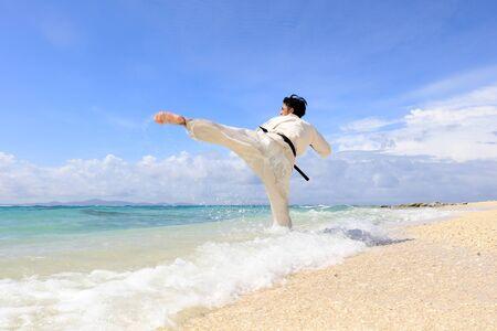 Young man practicing karate at beach