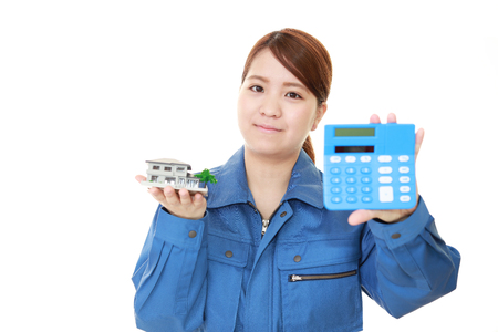 工場の女性労働者が電卓を保持しています。