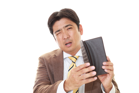 inattention: One Asian man looking sad at his empty wallet.