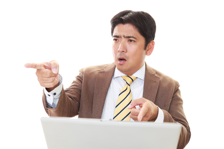 argues: Stressed and angry businessman work at laptop.