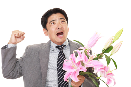 Handsome businessman holding flowers.