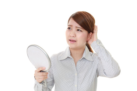 anaerobic: Young sad woman looking in the mirror at her wrinkles.