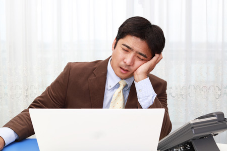 Tired and stressed Asian businessman