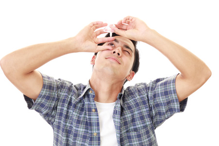 Man who puts eye drops in his eyes Stock Photo