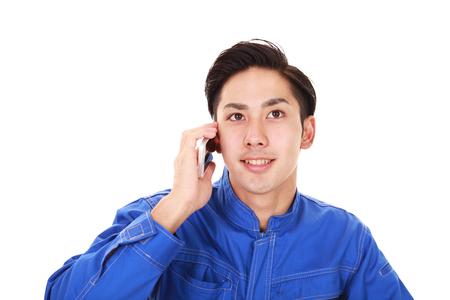 スマート フォンで話しているアジアの労働者 写真素材